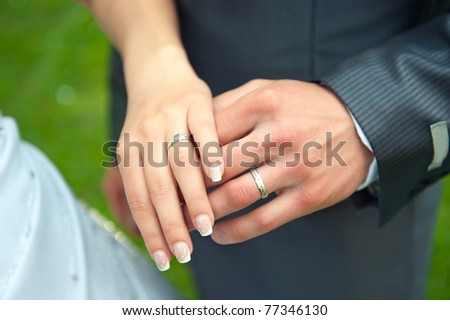 Loving couple holding hands with rings - stock photo