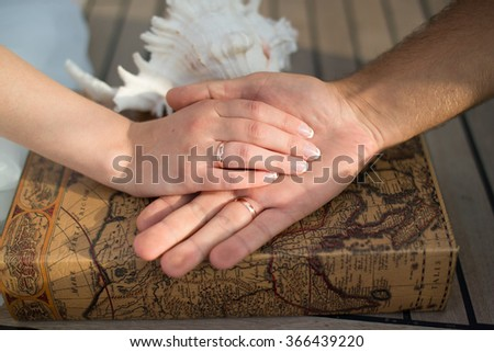 Loving couple holding hands with rings at the seashell, wedding theme, holding hands with love mood and tone