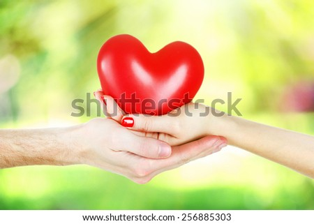 Loving couple holding heart in hands on sunny nature background
