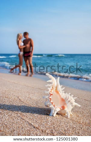 loving couple hug one another on the sea sand beach against big seashell - stock photo