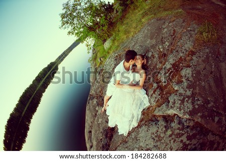 Loving couple hugging on the lake. Beautiful young woman and man in the background of nature. Happy smiling Loves a date - stock photo