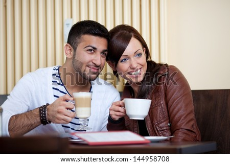 Loving couple in a restaurant sitting with their heads close together enjoying coffee and macchiato - stock photo