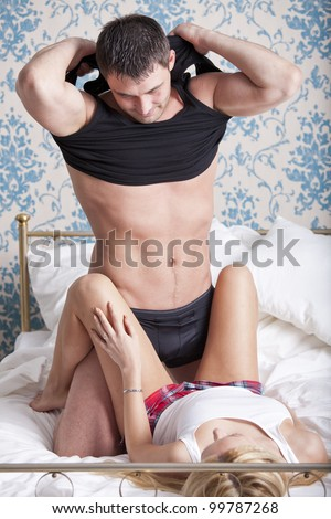 Loving couple in bed - man undressing underwear - stock photo