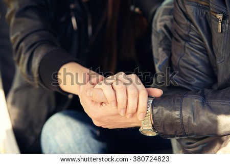 loving couple in black leather jackets hold each other by hands
