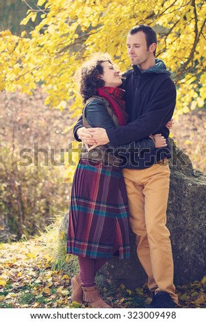 Loving couple in bright clothes hugging in autumnal park - stock photo