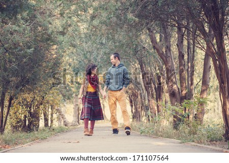 Loving couple in bright clothes walking along park alley holding hands and looking at each other - stock photo
