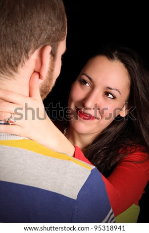 loving couple in f ront of black background - stock photo