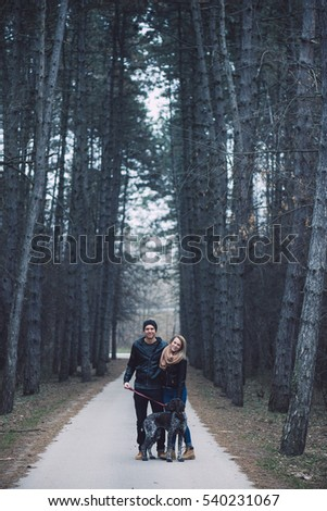 Loving couple in forest with cute dog. Happy couple in love posing outdoor.