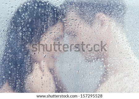 Loving couple in shower. Beautiful young loving couple hugging while standing in shower - stock photo