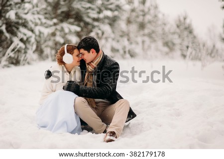 loving couple in the pine snowy forest - stock photo