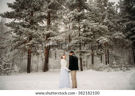 loving couple in the pine snowy forest