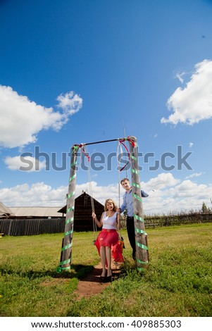 loving couple in the rural landscape. woman in a red dress and a man in a blue shirt