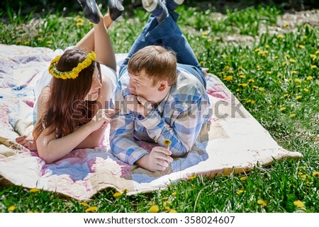 loving couple in the spring garden on a picnic blanket to lie.