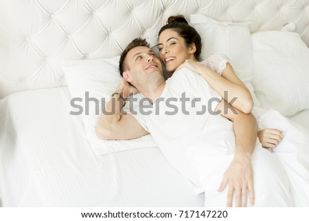 Loving couple in the white bed