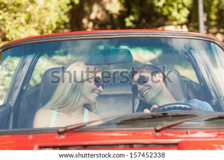 Loving couple in their red cabriolet having a ride on sunny day - stock photo