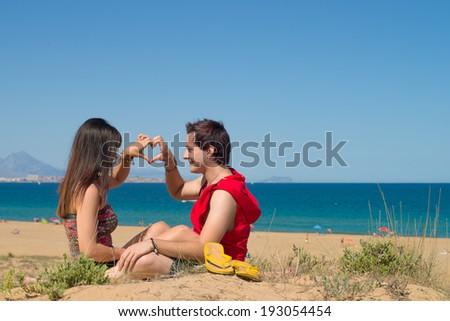 Loving couple in their twenties on the beach - stock photo