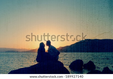 Loving couple kissing at the sea in the evening. Filtered image: vintage, grunge and texture effects - stock photo