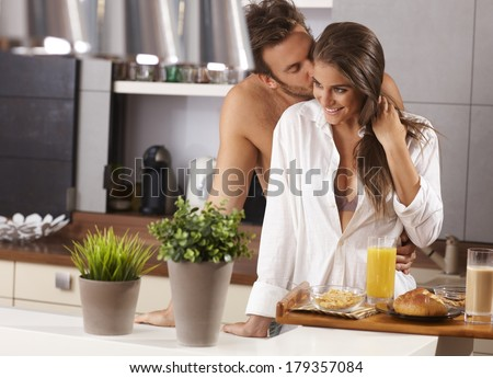 Loving couple kissing in the kitchen in the morning. - stock photo