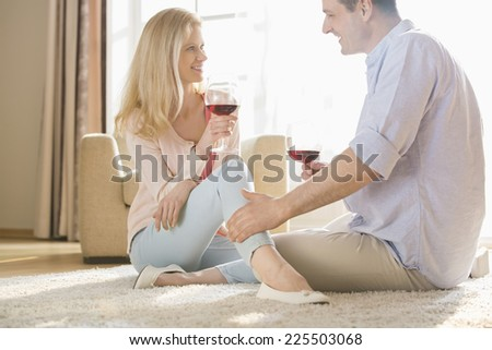 Loving couple looking at each other while drinking red wine at home - stock photo