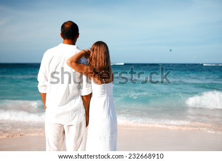 Loving couple looking the ocean. Romantic vacation.