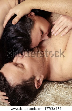 Loving couple lying on a bed - stock photo