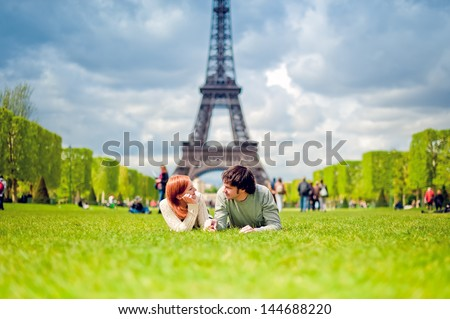 Loving couple lying on the grass on the Champ de Mars in Paris with the Eiffel Tower in the Background - stock photo