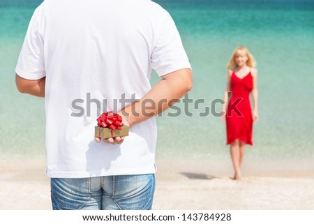 loving couple - man with gift surprise for his woman on sea beach - the romantic date or birthday or valentines day concept - stock photo
