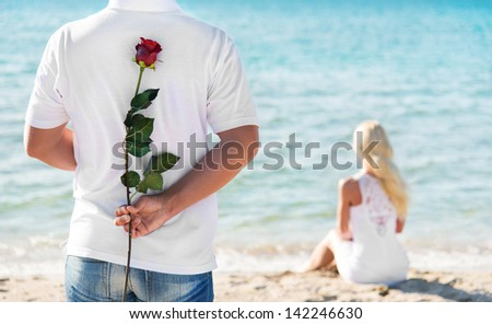 loving couple - man with rose waiting his woman on the sea beach at summer - the romantic date or wedding or valentines day concept - stock photo