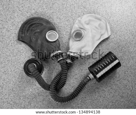 Loving couple of gas masks looking at each other - stock photo
