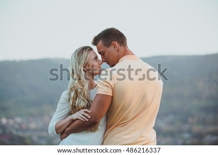 Loving couple on a walk. The boy and girl look lovingly at each other. Lovers hugging. A date outdoors in the evening. Sunset landscape. Horizontal photo.