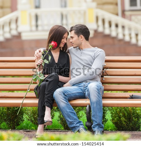Loving couple on the bench. Cheerful young couple sitting close to each other and smiling - stock photo