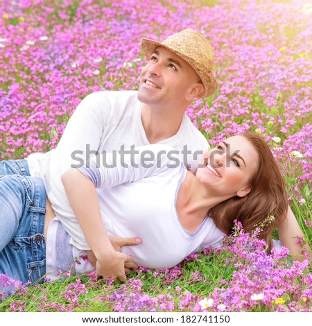 Loving couple on the fresh purple floral field, cuddling outdoors in sunny day, enjoying each other, young family, romance concept - stock photo
