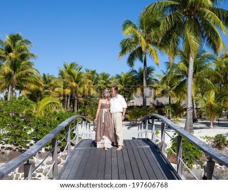 Loving couple on the wooden bridge on the tropical island - stock photo