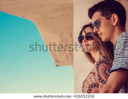Loving couple posing under blue sky. - stock photo