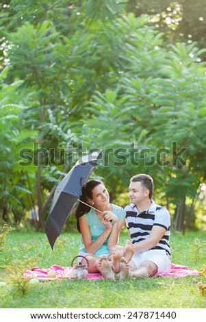 Loving couple relaxing on a picnic. Girl holding an umbrella in his hands.