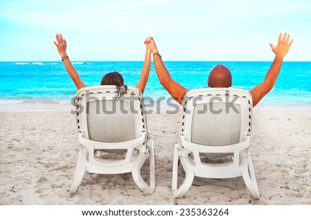 Loving Couple relaxing on sunbed. Summer Vacation - stock photo