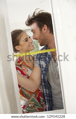 Loving couple renovating home, measuring by ruler, smiling happy. - stock photo