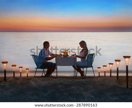 Loving couple share a romantic dinner with candles, lanterns and wine glasses at sea beach sand against wonderful sunset