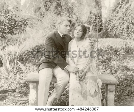 Loving couple sitting on bench in park