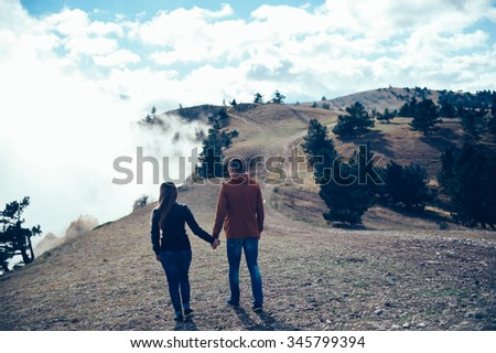 Loving couple sitting on mountain meadow and enjoying view of nature at sunny day in autumn