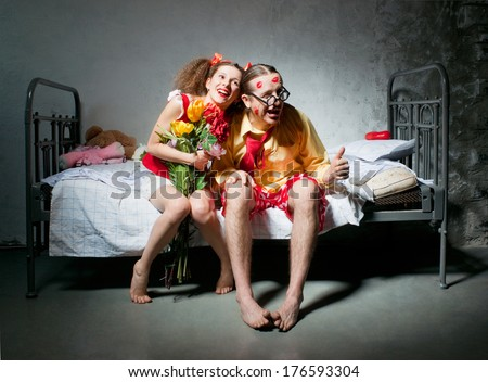 Loving couple sitting on the bed - stock photo