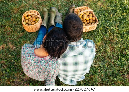 Loving couple sitting on the grass in autumn after picking apples. Top view