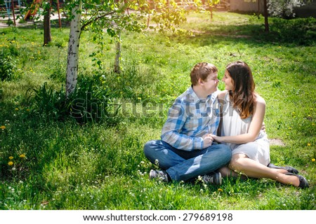 Loving couple sitting on the grass in the spring sunny day.
