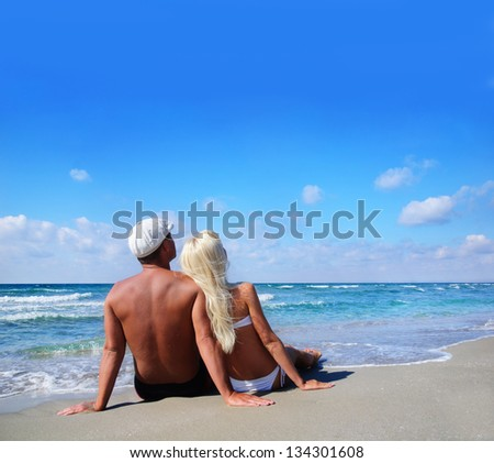 loving couple sitting on the sea sand beach and look at the blue sky