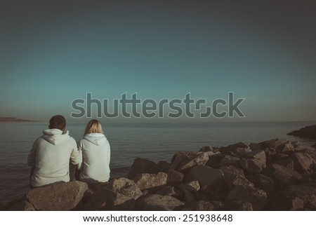 Loving couple sitting on the sea shore. Book cover