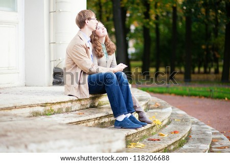 Loving couple sitting on the stairs together - stock photo