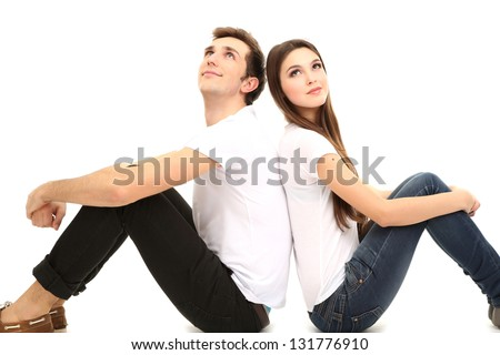 Loving couple sitting with back to each other on floor isolated on white - stock photo