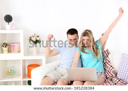 Loving couple sitting with laptop on sofa, on home interior background - stock photo