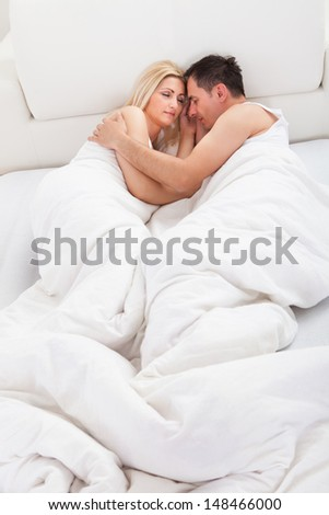 Loving Couple Sleeping Lying In Bed At Home - stock photo