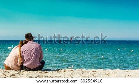 loving couple spending leisure time together at beach hugging rear view - stock photo
